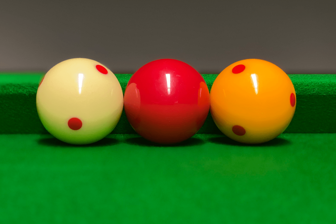Billiard balls lined up along the cushion